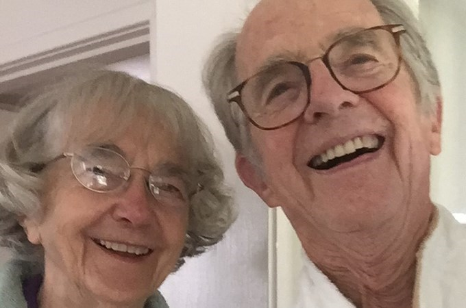 A couple, both wearing glasses, smile and take a selfie together.