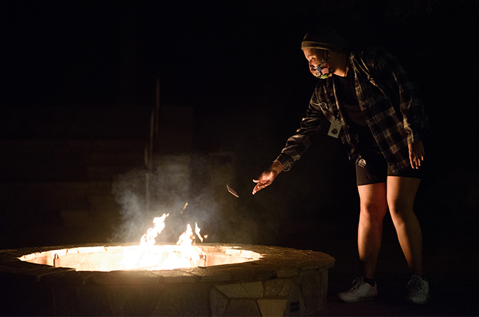 A student throws a piece of paper into a bonfire at night.