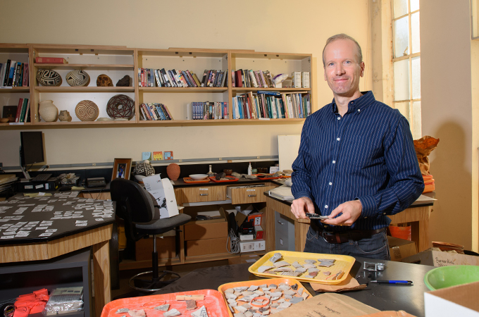 Professor Bernardini stands in his office with artifacts on display.