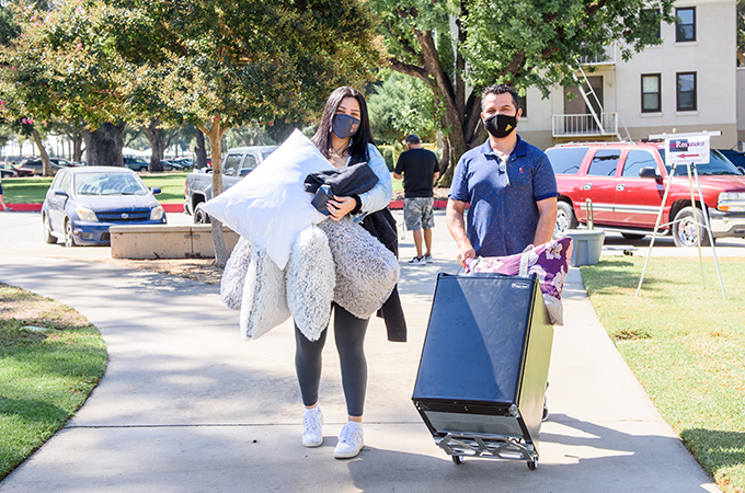 A student moves belongings into her residence hall, with help from family members and friends.