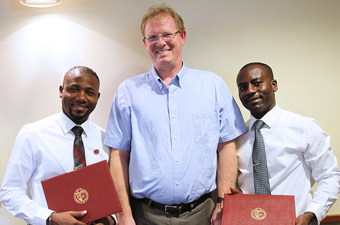 Haitian scholars Professor Herns Celestin (left), Professor Eudras Ceus (right) and Dean Andrew Wall (center).