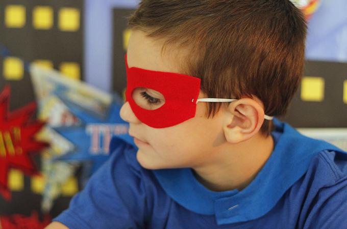 A child wears a superhero mask.