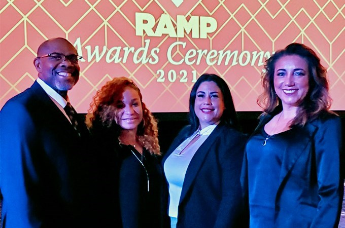 Four people stand together in front of a presentation screen at an award ceremony.