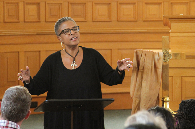 Yvette preaches to an audience from behind a church podium.