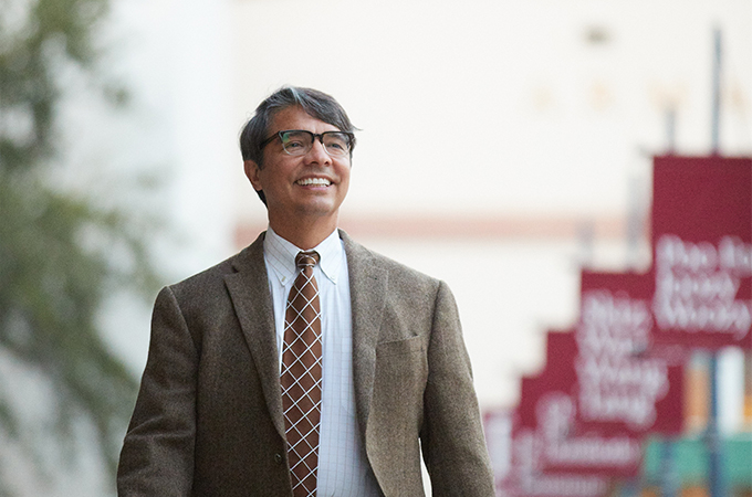 the dean of the school of education smiles while walking