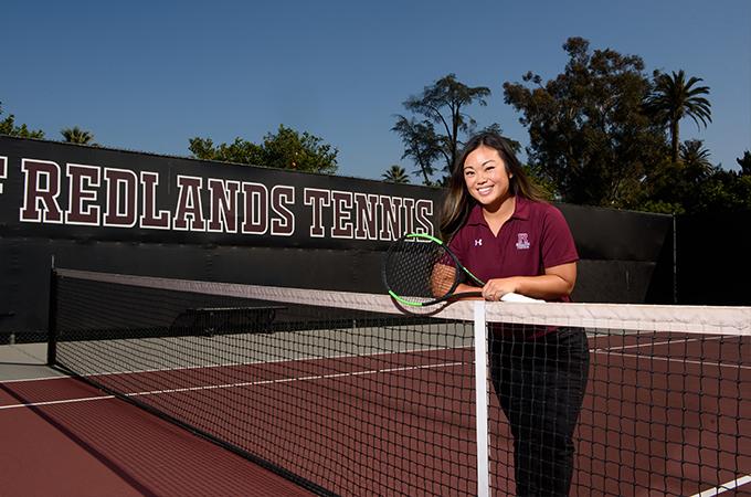 Lauren Villanueva leans against a net on the tennis court, holding a racquet in her hand.
