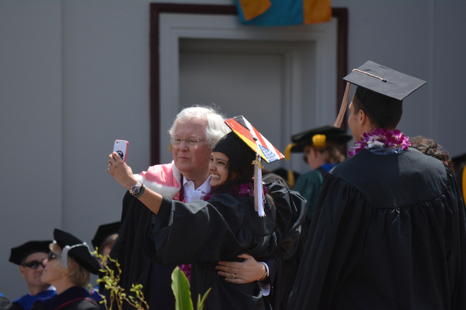 Professor Jack Osborn congratulates a student on the stage during a Commencement ceremony.