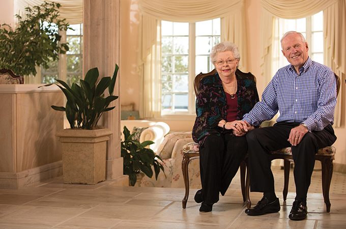 The Hunsakers sit in the foyer of a grand room, holding hands and smiling.