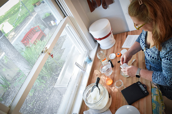 Candace Glendening measures substances for a science project in her home kitchen during the COVID-19 pandemic.