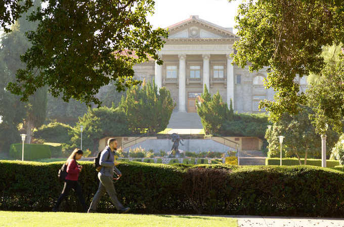 Two people walk in front of the Administration Building and REDLANDS lawn