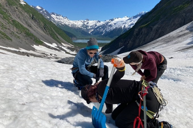 Three people perform scientific research on a glacier in Alaska.
