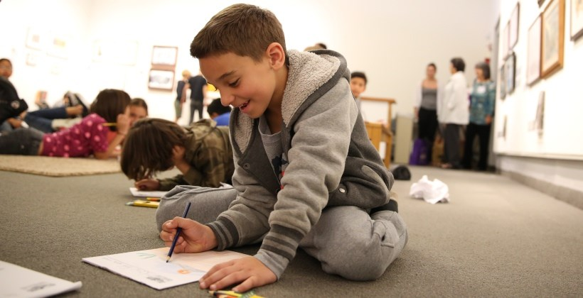 Zecharia Saha, a third-grade McKinley Elementary School student, draws during the 20th annual Charlotte S. Huck Children's Literature Festival.