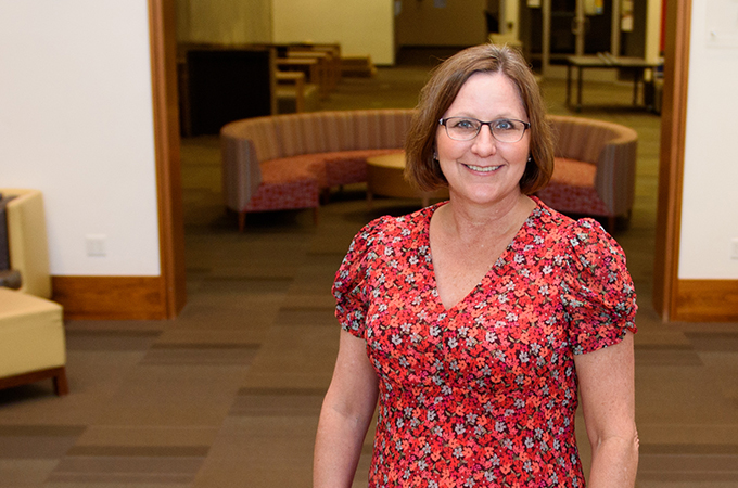 Cindy Tengler stands on the stairs leading to the library foyer.