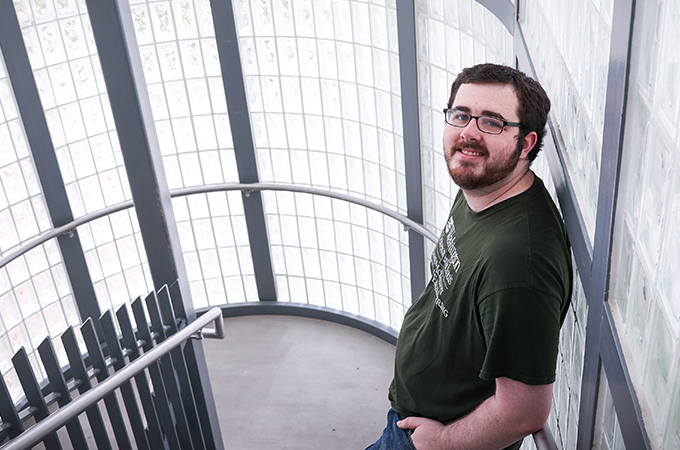 Jacob Griffin leans against a wall of glass tiles in a stairwell.