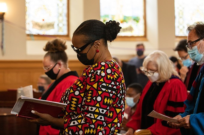A group of people stand in a sanctuary and look at hymnals.