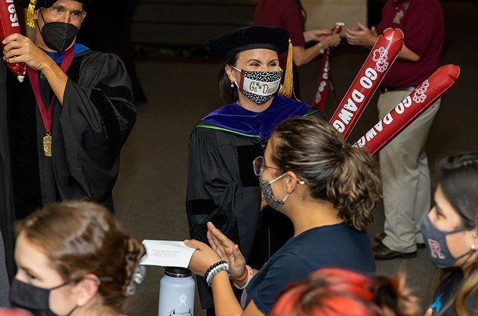 President Newkirk celebrates students as they walk into the Memorial Chapel.