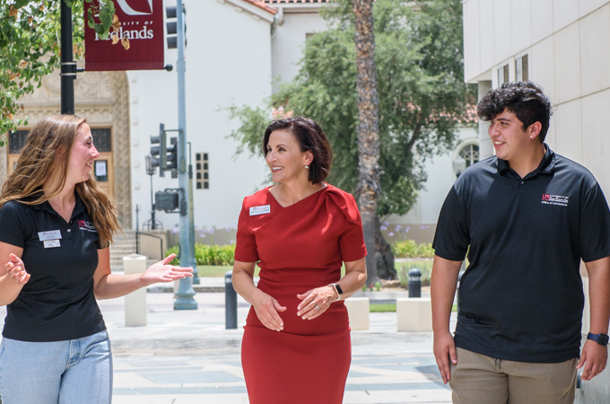 President Newkirk walks through Hunsaker Plaza, flanked by two students.