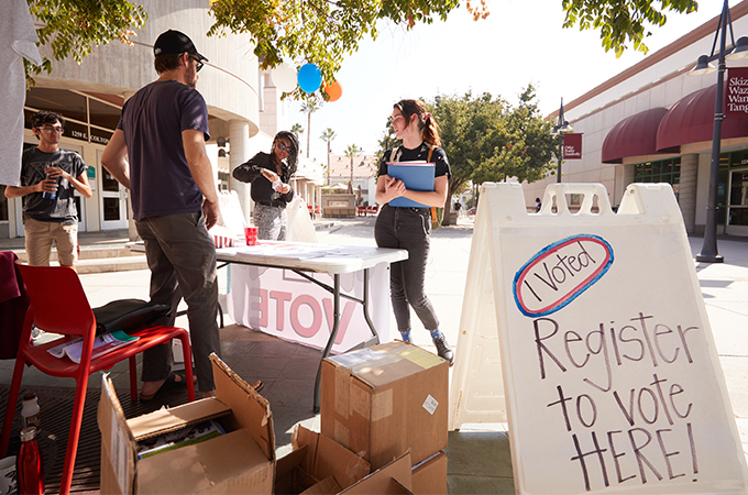 Students talk with a professor and register to vote in Hunsaker Plaza.