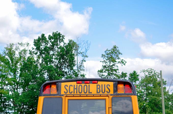 The rear facade of a yellow school bus.