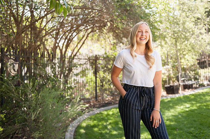 University of Redlands student Sadie Pickering poses in a garden.