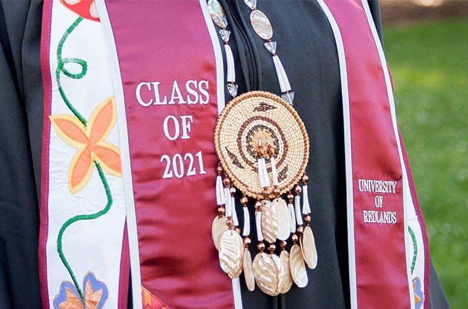 A student pairs a traditional Native American necklace with their Class of 2021 Commencement sash.