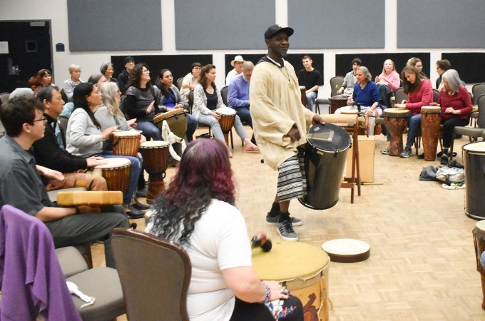 Drum circle participants play a variety of drums from around the world, as musician Marcus Miller (center) offers words of encouragement. (Photo by Carlos Puma)