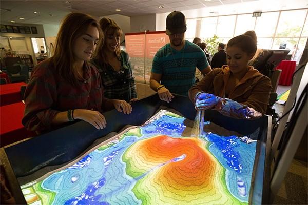 Students using Augmented Reality Sandbox