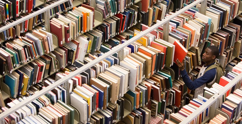 Student surrounded by tons of books on shelves