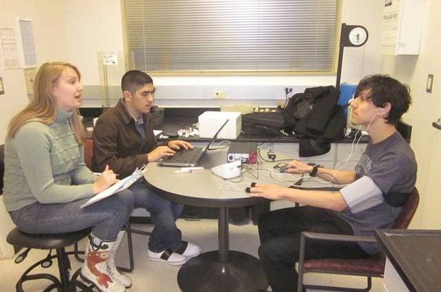 Undergraduate researchers administer a protocol on student research subjects.