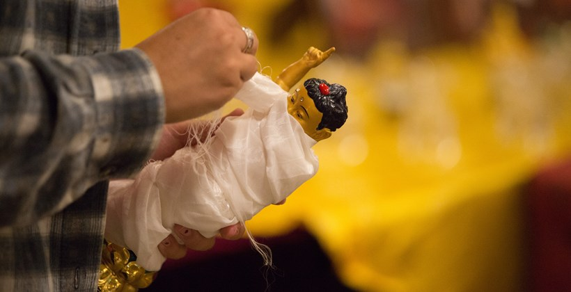 carefully wrapping a small buddhist relic