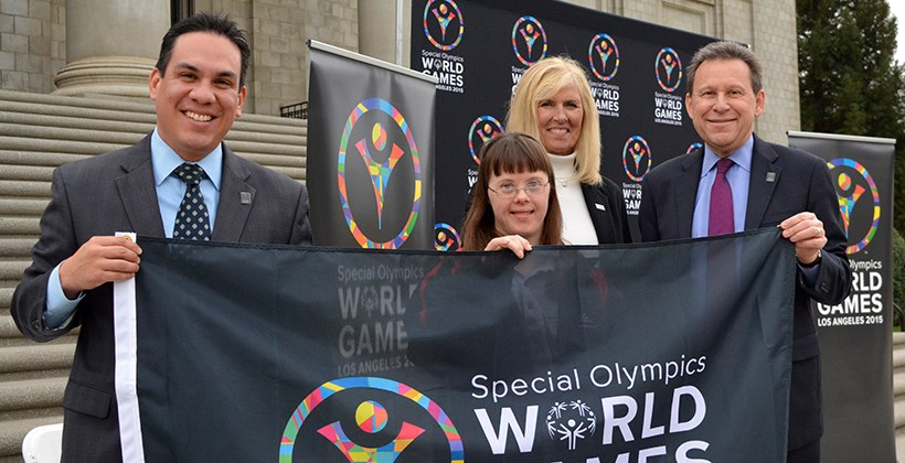 President Kuncl holding Special Olympics banner