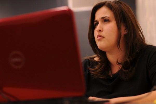 Woman taking notes on laptop