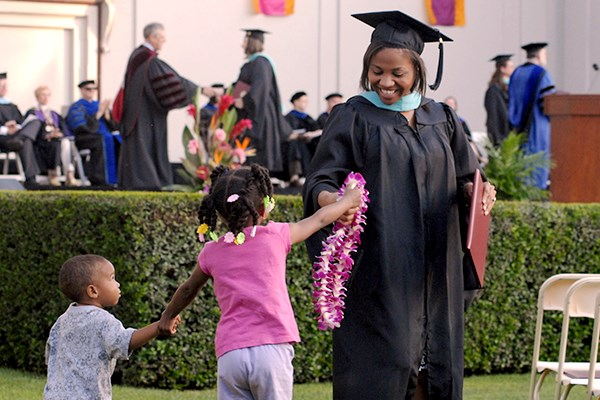 School of Education graduate being handed a lei by child during commencement.