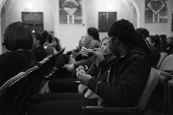 U of R Professor Renée Van Vechten shares a moment with a fellow attendee taking communion.