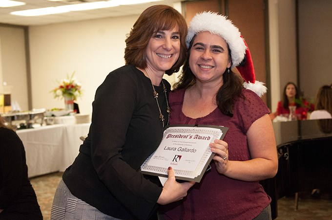 Laura Gallardo '03 (right), director of donor relations and interim director of advancement communications, accepts a President's Award.
