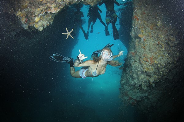 """Melissa Atkins '15 makes a free-diving entrance to """"The Blue Room"""" cave. (Photo by Ron Leidich)"""