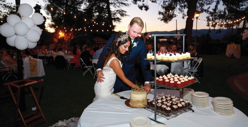 Bride and groom at reception dessert table