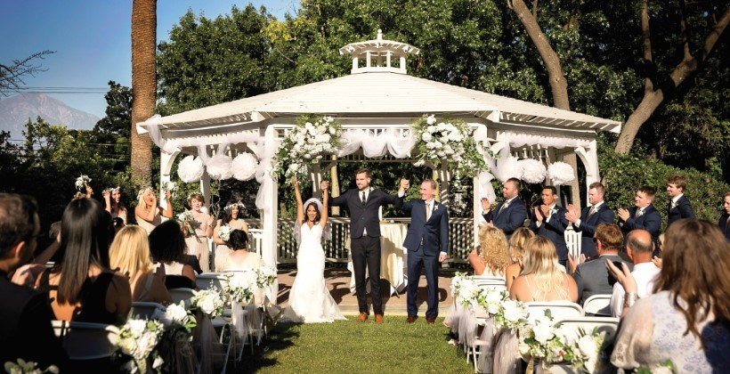 Wedding party and guests in front of white gazebo