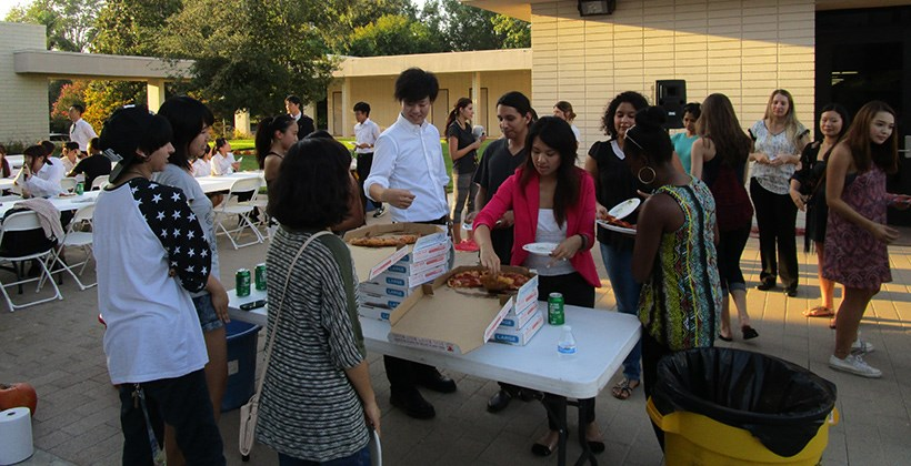 Truesdail students and Japanese student visitors eat pizza